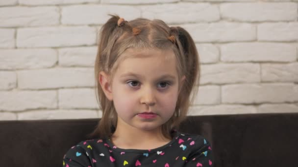 Close-up portrait of a little girl, carefully looking at the TV screen or the interlocutor.
