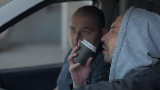 Zwei Männer, die in einem Auto sitzen und ein Foto mit einer professionellen Kamera, einem Privatdetektiv oder einem Paparazzi-Spion machen.