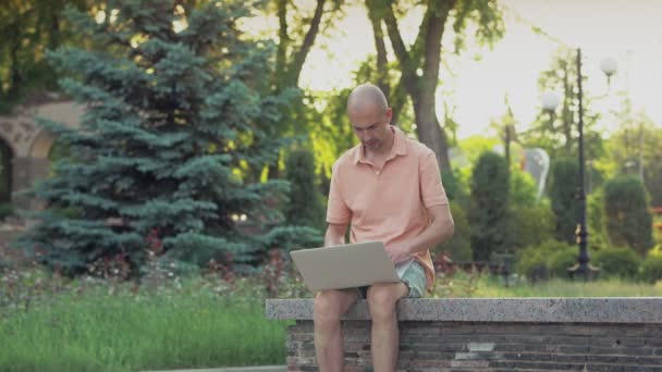 Egy férfi ül a parkban és laptoppal dolgozik..