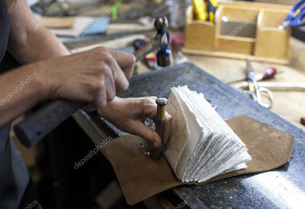 Bookbinder hammers hardware to back of custom book.
