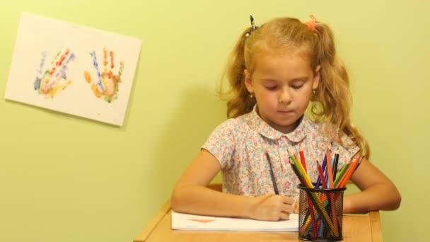 Roztomilá dívka nakreslí obrázek.