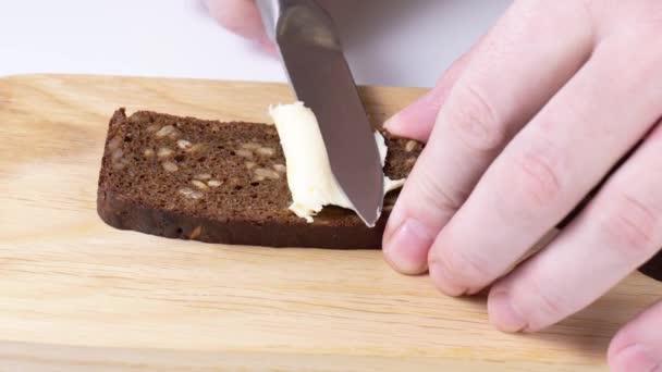 vajat szórni a kenyérre egy késsel közelkép