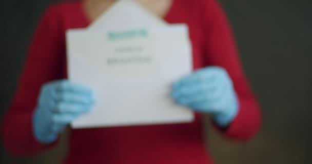 Žena drží negativní test na detekci protilátek na Covid-19. Push In neidentifikovatelné osoby nosící masku obličeje a modré chirurgické rukavice zobrazující otevřenou obálku s negativními výsledky koronavirových testů.