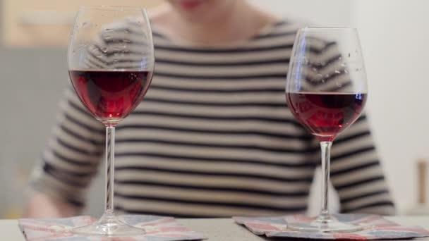 Dvě sklenky červeného vína. Dívka v pruhované tričko v pozadí.