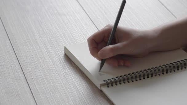 Női kéz írja egy jegyzetet a notebook. Egy levelet egy barátom. Költészet a visszavert fény. Gyors írás.