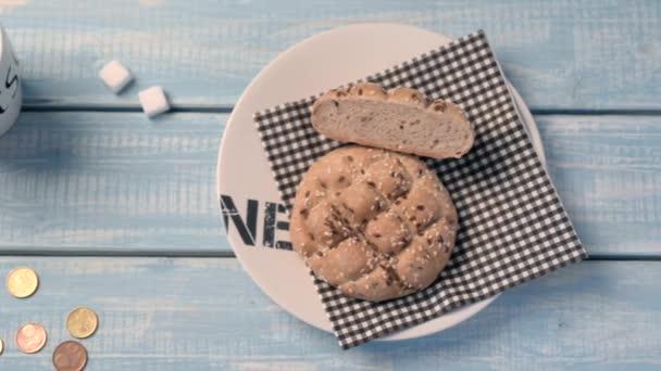 Poco costoso panino, una tazza di caffè e due fette di zucchero su un tavolo in legno blu. Il costo minimo