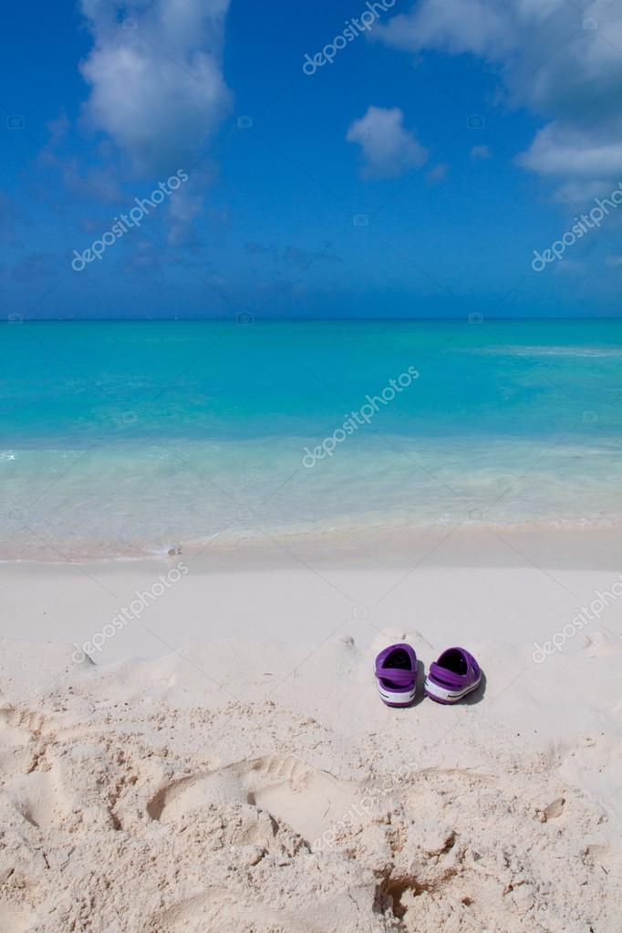7fced23f6 Pair of colored sandals on a white sand beach — Stock Photo © scris ...