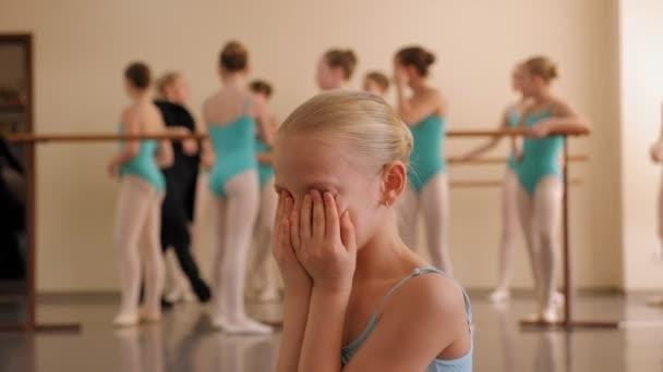 A little ballerina cries in a ballet dance Studio during a class.