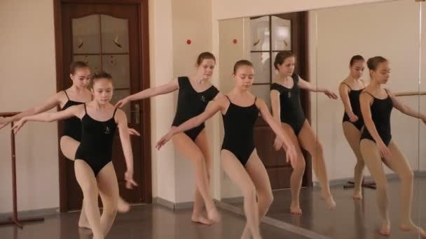 Egy csapat fiatal balerina fekete fürdőruhában, akik balett stúdióban próbálnak..