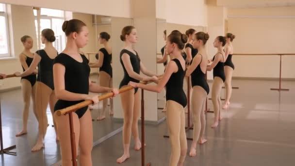 Egy csapat balett lány táncóra előtt nyújtózkodik..