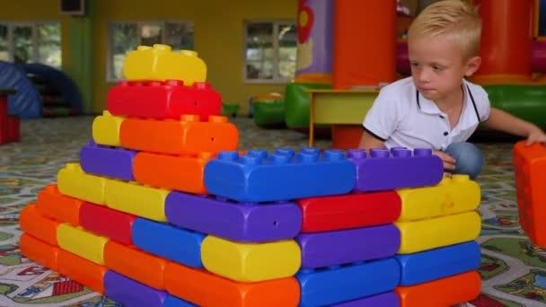 Malý chlapec hraje v dětském herním centru s konstruktérem.
