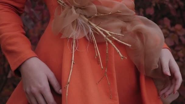 Egy vörös hajú fiatal nő egy csokor száraz náddal pózol az őszi erdőben..