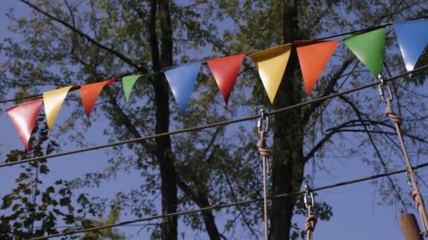 Színes zászló koszorúk kötél park nyáron.