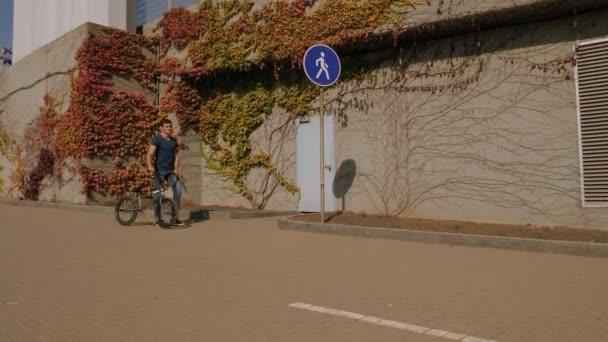 A teenage guy walks through the Park and holds his BMX bike. Bike sport.