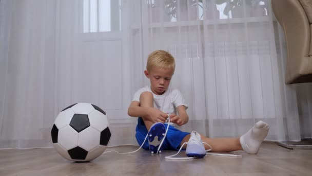 A little boy sits on the floor and learns to tie the laces on football boots.