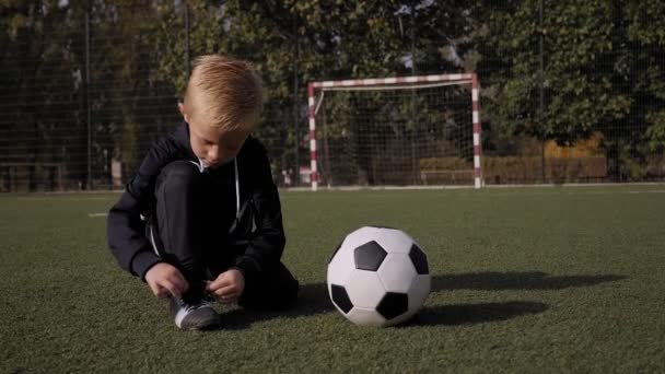 A little boy soccer player ties his shoelaces on a football field.