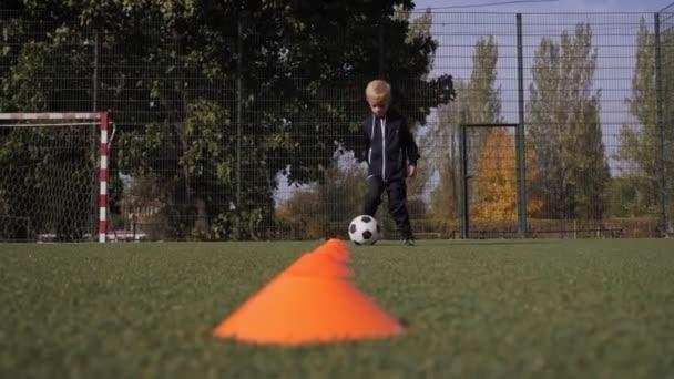 Malý chlapec trénuje v driblování mezi pomerančovými kužely. Fotbalový trénink.