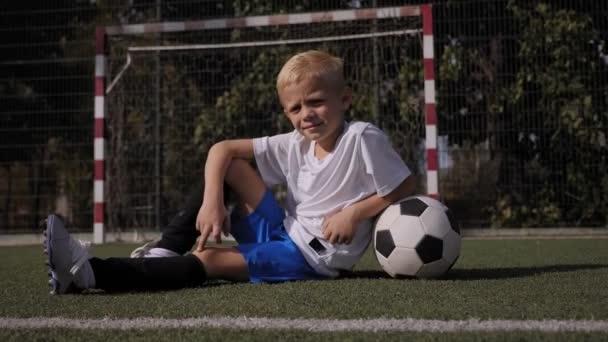 Portré egy kisfiúról a focipályán egy labdával, felemeli a hüvelykujját.