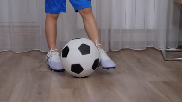 A little boy soccer player in blue shorts and soccer cleats trains at home.