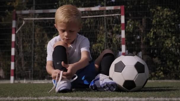 Malý fotbalista si zavazuje tkaničky na fotbalovém hřišti..