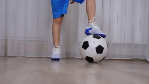 Detailní záběr malého chlapce ve fotbalových jamkách hraje doma s fotbalovým míčem.