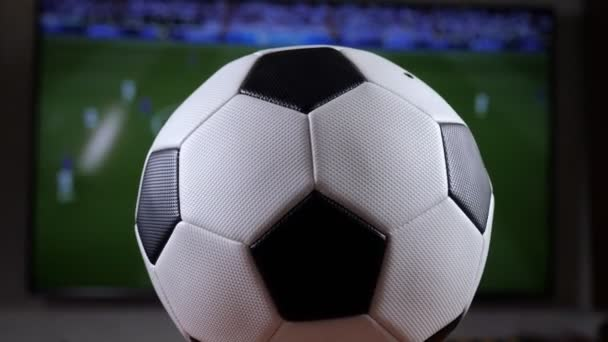A soccer ball spinning against the background of a TV with a football match.