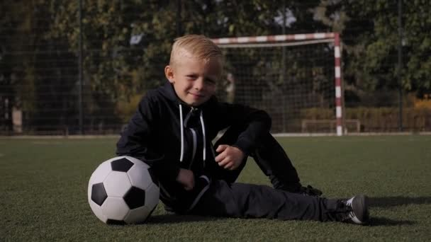 A little boy player sits on a soccer field with a ball and gives a thumbs up.