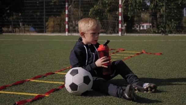 Malý chlapec sedí na trávě na fotbalovém hřišti a pije vodu z láhve.