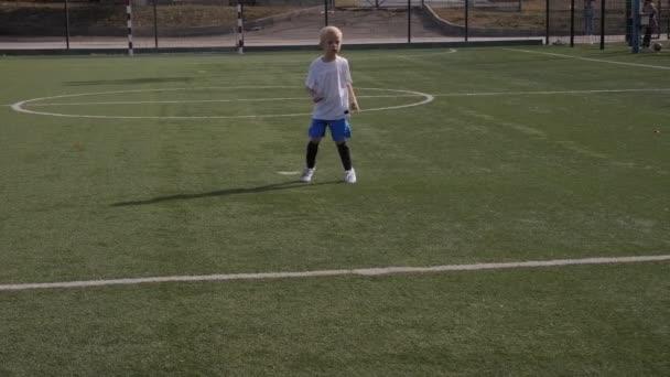 A little boy in a football uniform kicks a penalty on the football field.