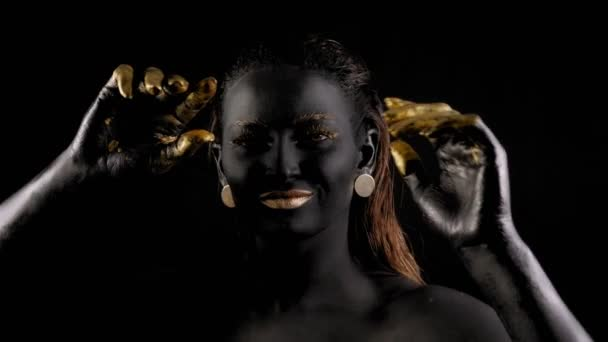 Fiatal meztelen nő, fekete-arany festékkel a testén és arccal táncol a sötétben