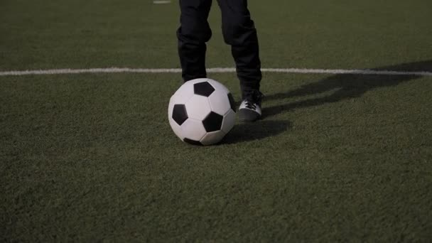 A little boy soccer player practices exercises with a ball on a football field.