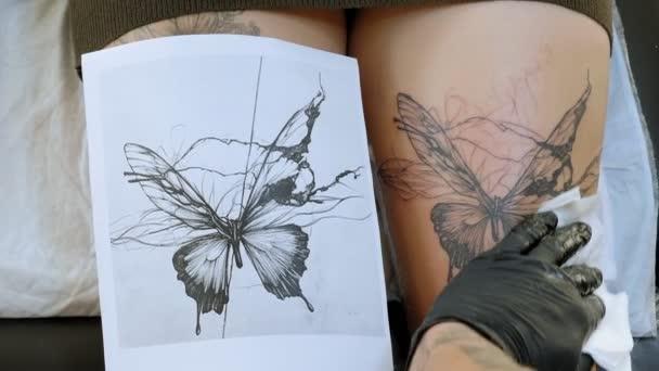A tetováló mester egy steril oldatot atomizál egy új tetováláson a női lábon..