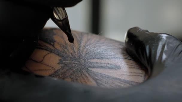 Közelkép egy fekete kesztyűs férfiról, aki egy fiatal nő lábán tetovál..