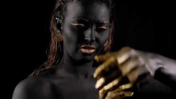 Portrét mladé ženy s kouzelnou černou pletí a zlatýma rukama.