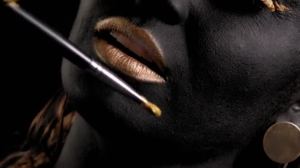 Közelkép egy nőről fekete-arany festékkel és egy festőecsettel a stúdióban.