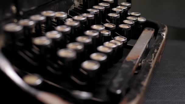 Close-up of a retro typewriter with old rusty buttons on a wooden table.