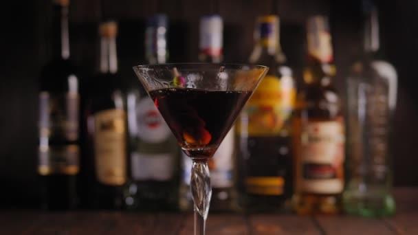 Detailní záběr růžové Martini sklenky s olivami na dřevěném baru.