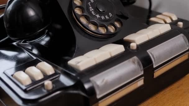 Ročník černý telefon na starém dřevěném stole pozadí.