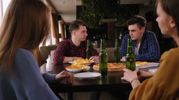 Skupina mladých lidí odpočívá v kavárně, pije pivo, jí pizzu a mluví..