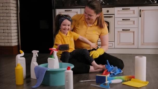 Eine glückliche Mutter mit einer Tochter bereitet sich darauf vor, das Haus aufzuräumen, lachen sie.