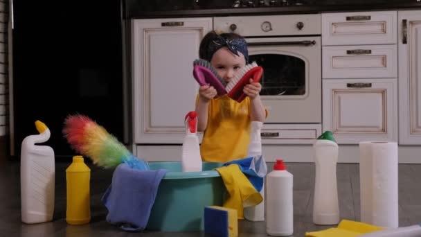 Nettes kleines Mädchen spielt mit Pinseln und Lumpen zum Putzen auf dem Boden sitzend