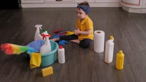 Veselá holčička si hraje doma s čisticími prostředky a čisticími kartáčky