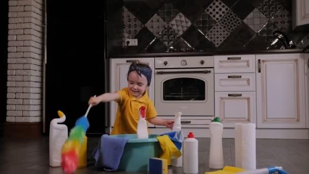 Ein fröhliches kleines Mädchen spielt zu Hause mit Waschmitteln und Putzbürsten