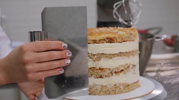 Detailní záběr cukrář zarovnává okraje smetanového dortu s velkou kovovou špachtlí
