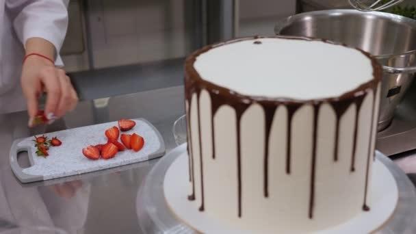 Šéfkuchařka krájí jahody nožem na krémový dort s čokoládou.