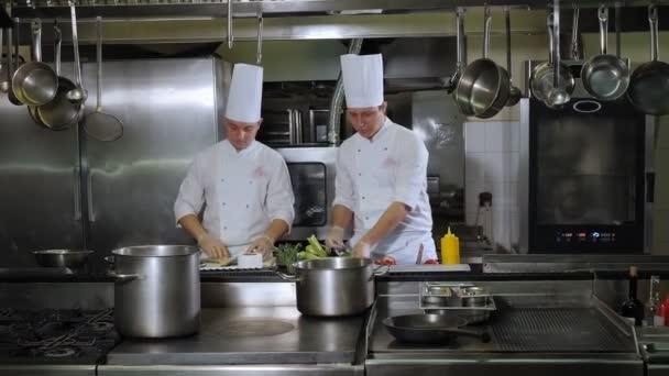 Dva kuchaři vaří ryby a zeleninu společně v kuchyni restaurace