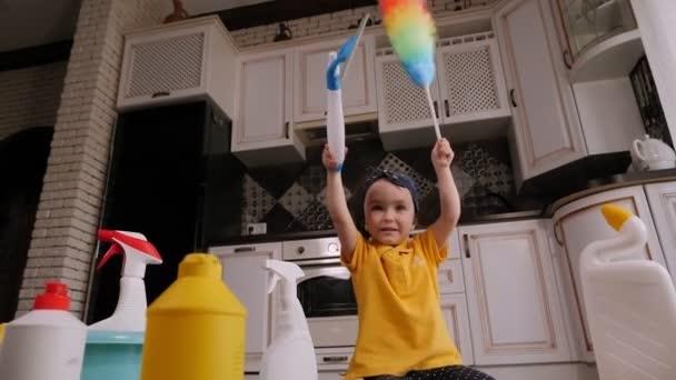 Detailní záběr malé holčičky hrající si v kuchyni s pracími prostředky a štětci.