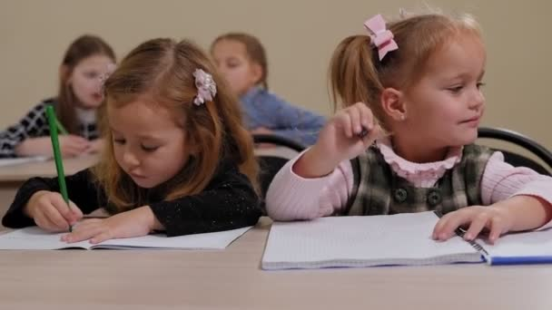 Little children sit at a desk in elementary school and draw in notebooks.