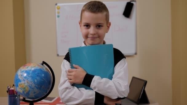 Portrét studenta se zápisníkem ve škole poblíž tabule a zeměkoule.