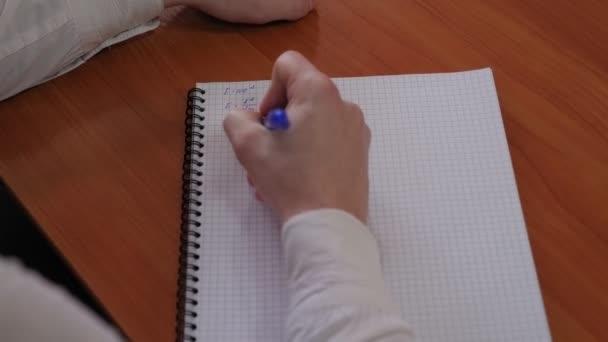 Közelkép egy diákról, aki matekfüzetbe ír, miközben egy íróasztalnál ül..